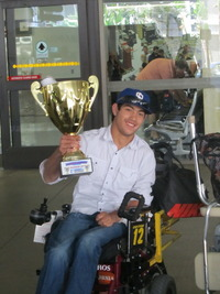 male athlete with blue cap and white shirt holding up a large gold trophy