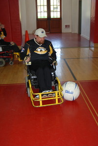 Brian MacLaren in his Strikeforce chair and black and gold jersey looking down at the ball
