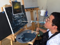 Artist Joe Haake painting with adaptive paintbrush in his mouth applying paint to the canvas sitting on easel