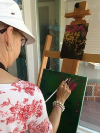Artist Erin Ziegler painting a pink flower with a green background on small canvas on easel