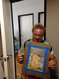 Artist Scott Ryker holding up a self portrait watercolor painting