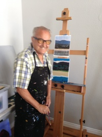 Artist Robert Winans wearing a black apron and standing in front of his landscape painting on an easel and smiling