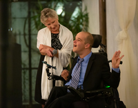 Gus A. is a man in a wheelchair with his mother Martha on stage giving a speech and holding a microhphone