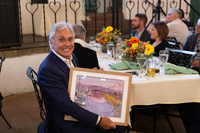 former President and CEO of UCPLA Ron Cohen smiling at the camera and holding a framed watercolor painting of the Santa Barbara harbor