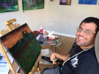 Artist Joe Haake sitting in front of his landscape painting on easel and smiling