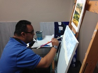 Artist Juan Perez looking at his easel with a paintbrush in right hand