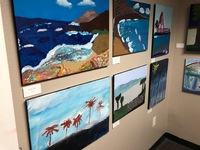a studio wall with several beach scene paintings hung on exhibition