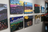 a studio wall with several landscape paintings hung on exhibition
