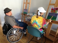 Studio Instructor Brian MacLaren sitting with artist Erin Ziegler while she paints at an easel