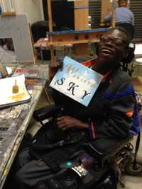 Artist Chuck Jefferson holding up a painting and poetry on canvas that he created