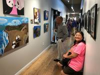 Artist Reiko Karl sitting in the gallery during 1st Thursday exhibition looking at her painting displayed on wall