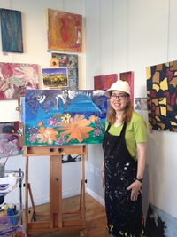 Artist Erin Ziegler standing next to her large painting inside the studio with art hanging on wall behind her