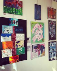 studio wall displaying several abstract and collage paintings
