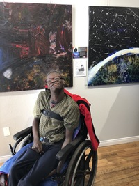 Artist Chuck Jefferson sitting near a display of his artwork in the gallery during 1st Thursday exhibition