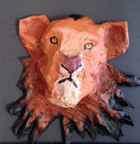 a paper mache head of a lion with bright orange fur and yellow eyes