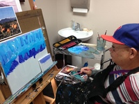 Artist Mike Gurney sitting in his studio ad painting at an easel