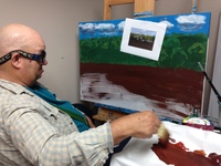 Artist Kyle Allan sitting in his studio and painting a landscape on an easel
