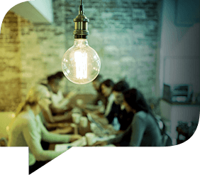 A lightbulb in front of employees working together while sitting at a table