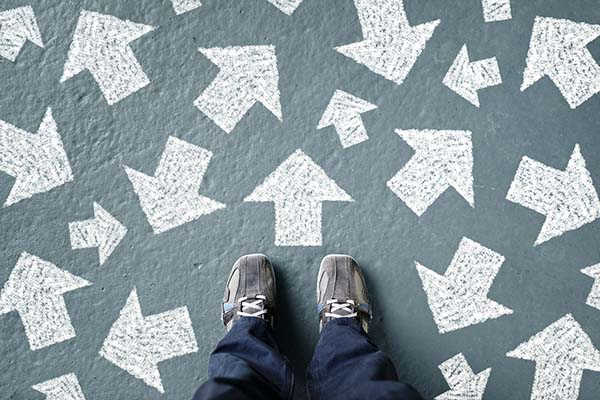 A person's feet are shown, surrounded by many arrows on the ground pointing in different directions.