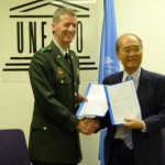 Major General Don T. Riley and Director-General Koïchiro Matsuura with the signed agreement