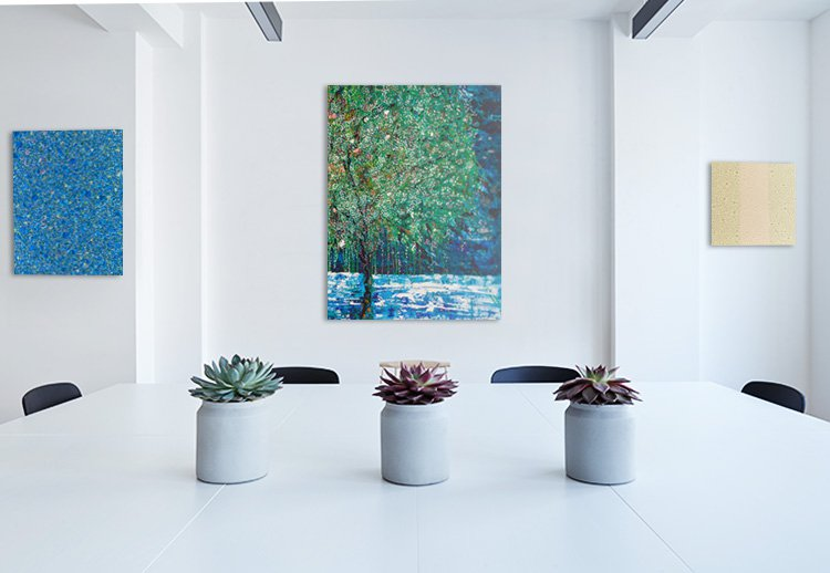 A conference table in a stylish office with paintings hung on the wall.