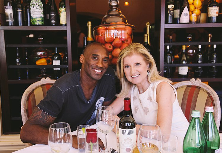 Arianna Huffington sitting with Kobe Bryant