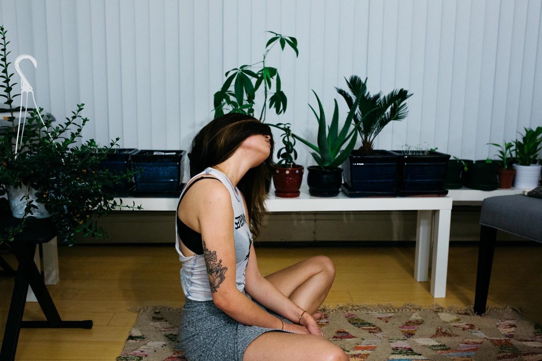 a woman sitting on a yoga mat, cross legged