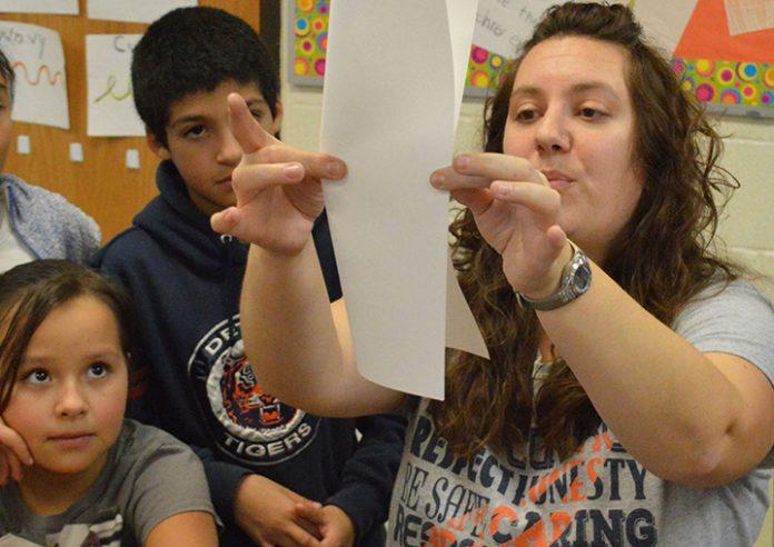 Art teacher Amber Warren shows, from left, Alexiana Ochoa and Alexis Odelin, how to make a name monster
