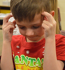 Kindergartner Visser uses his thinking cap while coming up with words to describe his teacher