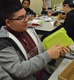 Ernie Peredo-Briceno prepares materials for his project