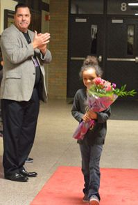 Superintendent Tom Reeder applauds as first-grader Kiara Thomas enters the building