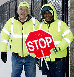 Steve Howell, a supervisor at All City Management Services, chats with crossing guard Kattie Eason at Martin Luther King Jr. Leadership Academy