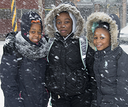 Happy after crossing busy Wealthy Street, with Eason's help, are eighth-graders (from left) Zaionna Love, Sharkia Caldwell and Kalyce Russell