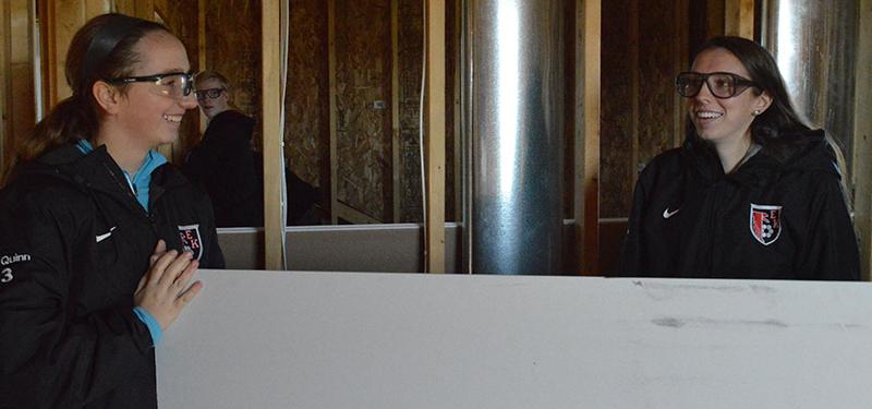 Seniors Allison Quinn and Chloe Quinn move a piece of drywall
