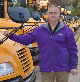 Don Hebeler, Wyoming Public Schools director of operations and support services, stands near the bus fleet. He and directors statewide need more drivers