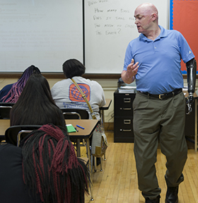 Algebra class at Innovation Central High School, with Colonel Bryan Forney explaining a math problem