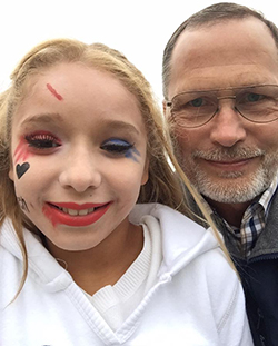 At a Halloween bash, David Britten poses sans makeup with a student
