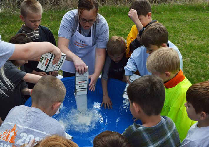 Science, technology, engineering and math teacher Kelly Behrens and students dump cornstarch into water