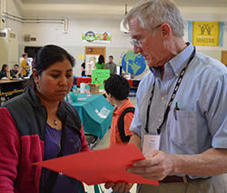 Ana Morales receives information about getting fresh produce this summer through Double Up Food Bucks from Gordie Moeller, food security advocate