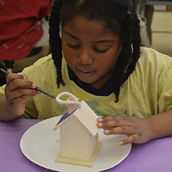 Kindergartner Areana Walton paints a birdhouse, an environment-themed project that ties to her community
