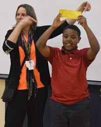 """LOOP and Coit Creative Arts Academy acknowledges student achievements with """"Mona Bucks."""" Site coordinator Kimberly VandenBerg gives fourth-grader Victor Thompson a golden ticket for his helpfulness"""
