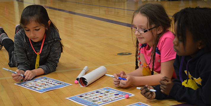 Second-graders (from left) Crystal Rios, Lyric McPhee and Nuru Nunda play a bicycle safety game