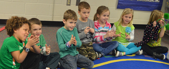 Kindergartners applaud for their guest readers