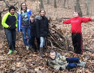 From left, fifth-grader Kahari Sprague, parent Jessica Rogers, and fifth-graders Christopher Rogers, Peyton Rike, Andrew Leet and Hope Kilbourn (front) with the lean-to they built
