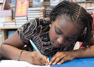 Oummu S. Kabba signs her books, which she began publishing at age 8