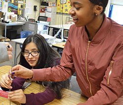 Seventh-graders Samatha Benitez and Camiyah Blackman try to figure out how to balance six nails atop one nailhead, a challenge from Mayor Stephen Kepley
