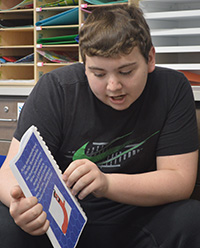 Freshman Logan Evans shares his book with second-graders