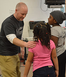 Kelly McGee, media specialist and theater director, tags a second-grader during his improv session