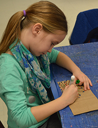 Second-grader Brynn Marshall colors a design on a paper bag