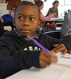 Tito Ekundat, a refugee student from the Congo, takes notes with his fifth grade class